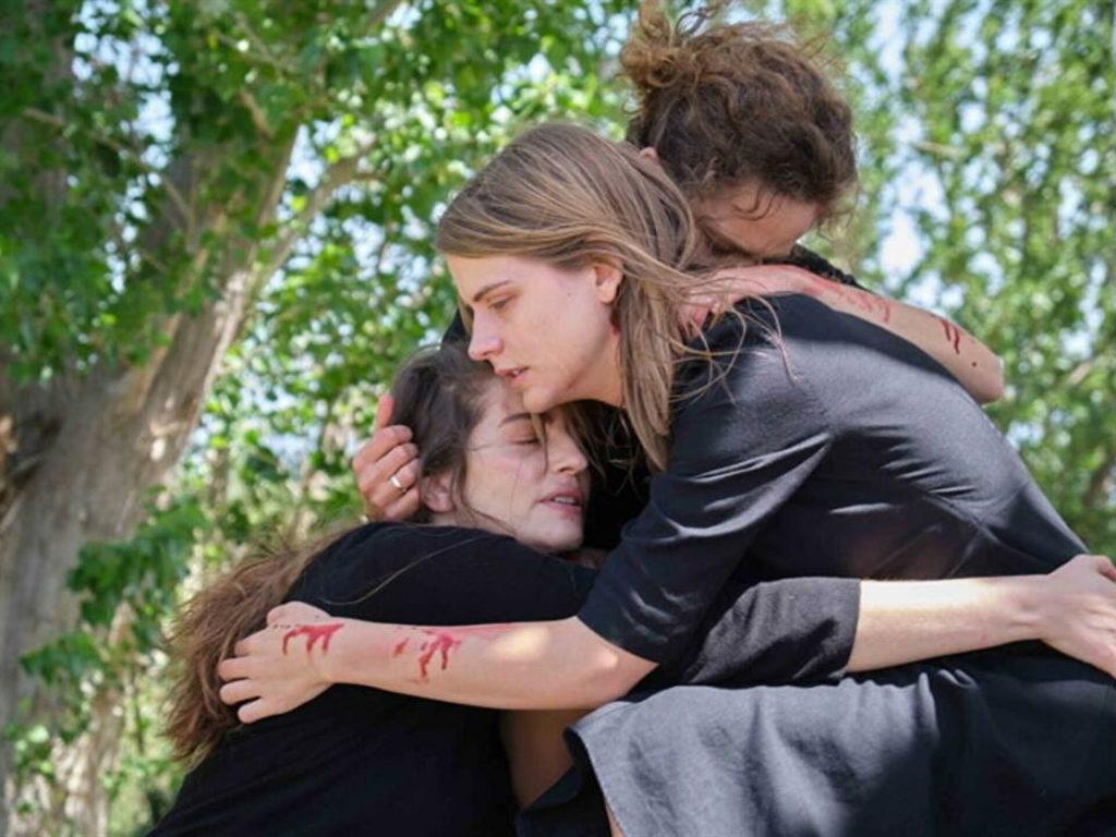 τρεις γυναίκες με ματωμένα ρούχα αγκαλιάζονται