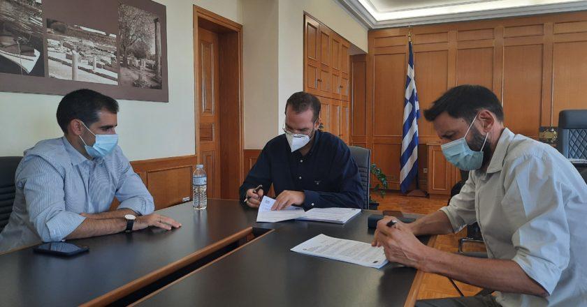 τρεις άνδρες κάθονται σε ένα γραφειο
